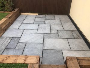 Indian Sandstone Patio with Sleeper Retaining Walls in Ongar, Essex
