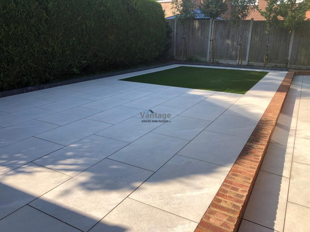 Porcelain Tiled Patio with Brickwall and Artificial Lawn in Chelmsford