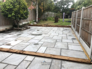 Tiered Sandstone Patio with Retaining Sleeper Walls in Chelmsford
